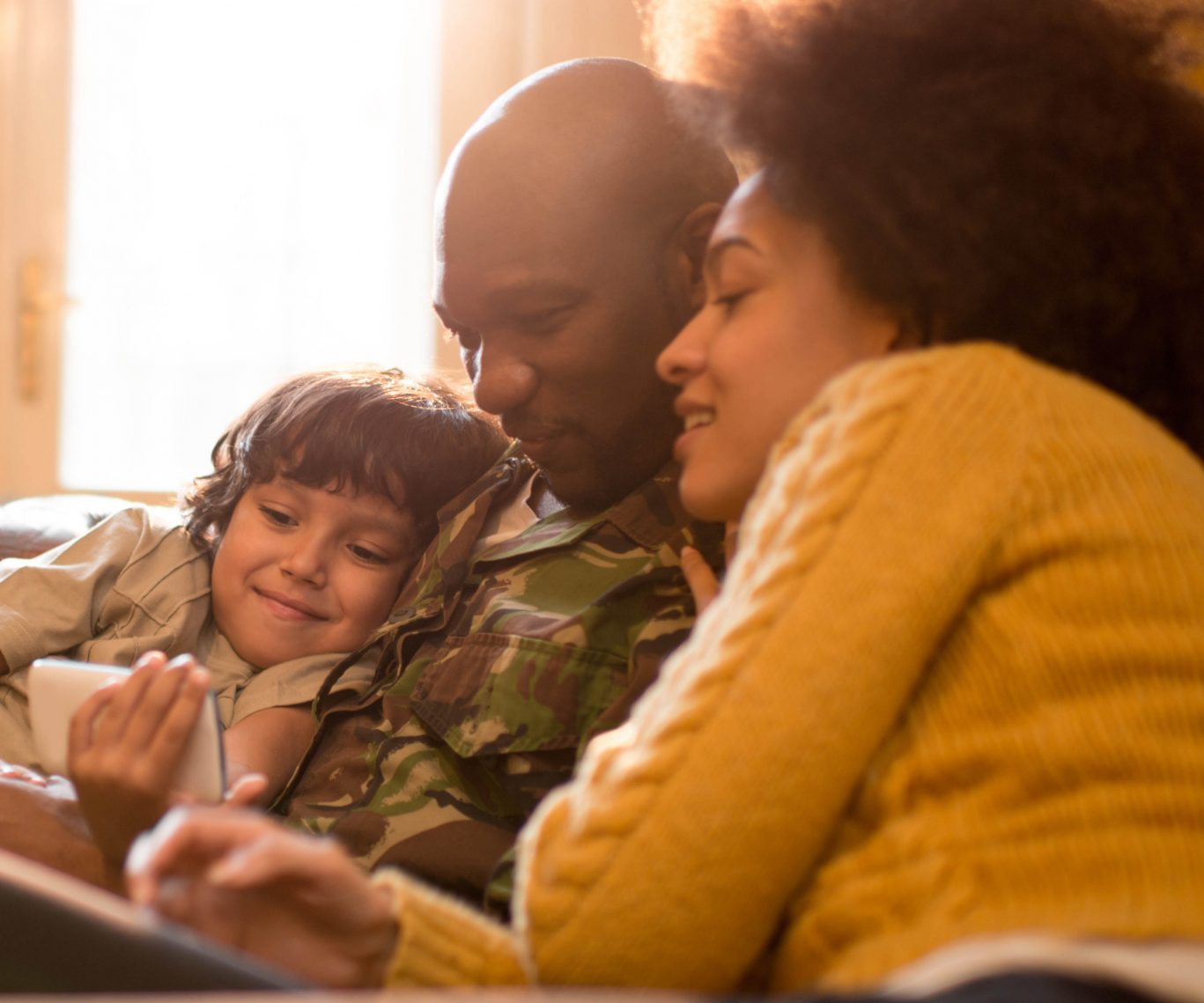 African American military family using cell phone at home.